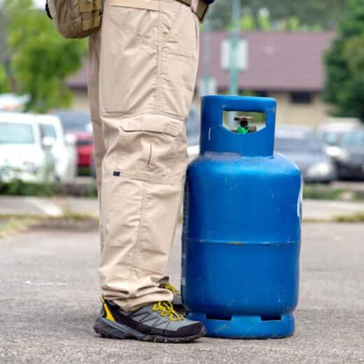 foto de homem carregando um bujão representando o vazamento de gás ou então o gás vazando